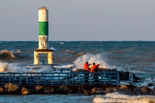 Rescue crews search Thursday for a 16-year-old girl who fell into Lake Michigan after a wave hit the pier at Holland State Park the night before.