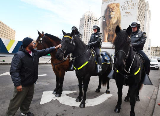 Detroiter Duane Jorman pats Detroit's newest equine police officer 'Mirah' on the nose while greeting three Detroit Mounted Police horses and their riders (from left) Cpl. Garnette Steen on Capone, Cpl. Sandra Chavez on Mirah and Cpl Mark Zajac atop Remi on patrol in Campus Martius in downtown Detroit Thursday.