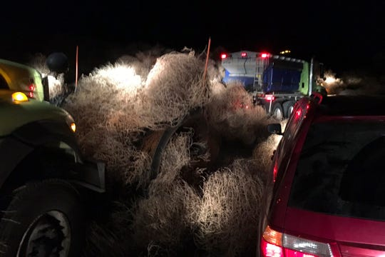 In this image taken Tuesday evening, Dec. 31, 2019, and provided by the Washington State Patrol, Washington State Department of Transportation using snow plows to remove a pile of tumbleweeds along State Route 240 near Richland, Wash.