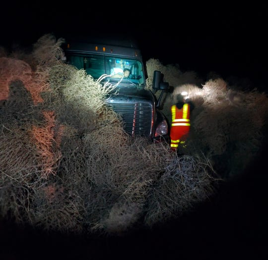 In this image taken Tuesday evening, Dec. 31, 2019, and provided by the Washington State Patrol, a vehicle is trapped by a pile of tumbleweeds along State Route 240 near Richland, Wash.
