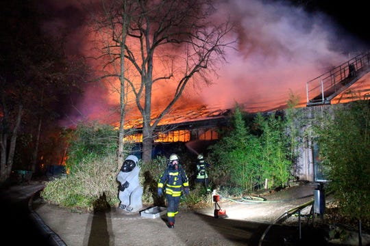 Firefighters stand in front of the burning monkey house at Krefeld Zoo, in Krefeld, Germnay, Wednesday Jan 1, 2020. A fire at a zoo in western Germany killed a large number of animals in the early hours of the new year, authorities said.
