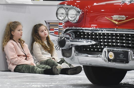 """Twins Hailey Melios, 9, and Hannah Mellios, """"I'm 50 seconds earlier,"""" look over a 1958 Cadillac Special as their parents work on the Cadillac display at the first annual Southeast Michigan Auto Show at Suburban Collection Showcase in Novi Thursday, where final preparations for the show were being done."""