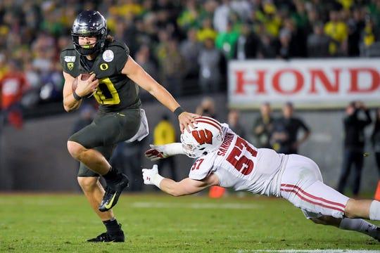 Oregon quarterback Justin Herbert runs for a touchdown past Wisconsin linebacker Jack Sanborn.