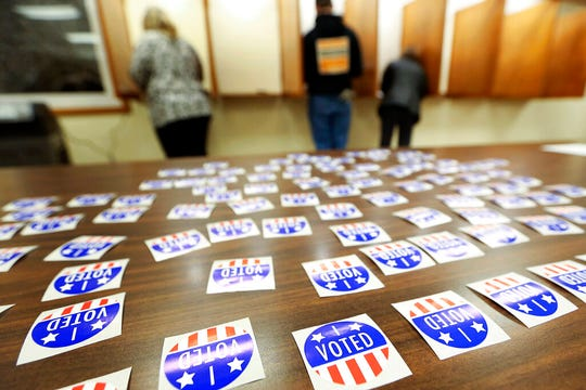 In this Nov. 6, 2018 file photo, people vote at Jamestown Town Hall in Kieler, Wis. Conservatives are asking a judge to find the Wisconsin Elections Commission in contempt for not immediately purging more than 200,000 voters from the rolls. A judge last month ordered the purge of voters who may have moved and didn't respond within 30 days to notification sent by the elections commission in October 2019.