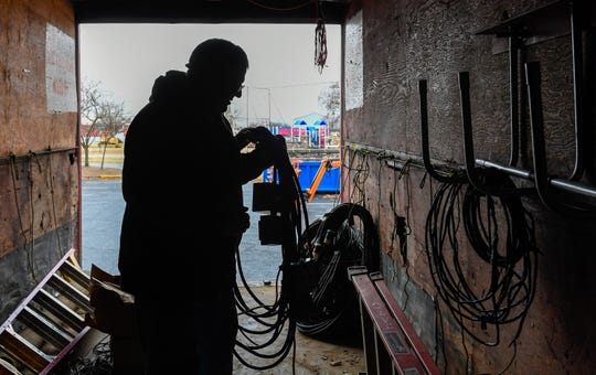 Silhouetted in the storage trailer, Ed Kiesel, Haubstadt, with the International Brotherhood of Electrical Workers Local 16, hangs up coils of electrical cable as he starts the disassembly process for the Ritzy's Fantasy of Lights in Evansville's Garvin Park Thursday, January 2, 2020.