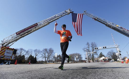 Dean Feaster gestures as he approaches the finish line of the 8th Annual Peacock Strides for Babies 5K Run