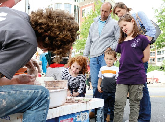 From left, Aynsley, Tucker and Audrey Barnett, watch with their parents Quay and Michelle Barnet as Conor Alwood of Clemson University molds a clay pot during Artisphere.