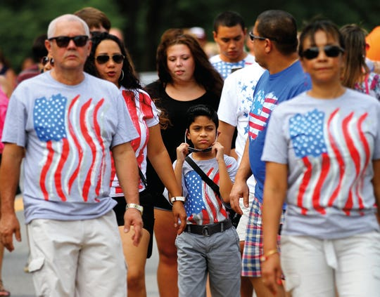 A group wearing matching American Flag t-shirts walk down Main Street during the Wells Fargo Red White and Blue Festival in downtown Greenville.