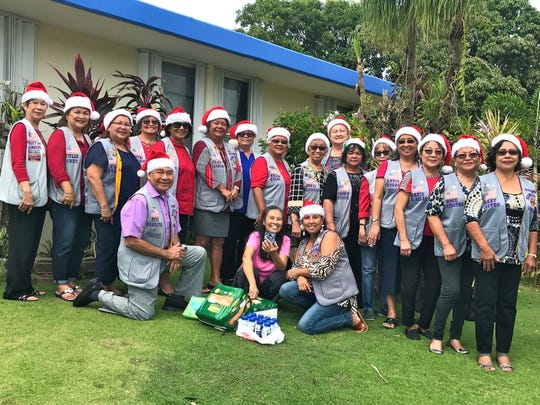 """In fulfilling its service project of """"caring for the sick and the elderly,"""" the Guam Sunshine Lions Club brought Christmas cheer, song, and supplies to Cirila Velasco, 94, of Yona on Dec. 21. From left: L. Pete Babauta, Cora Velasco (accepted supplies on behalf of her mother Cirila), and L. Tish Tano.  Standing from left: Lions Marietta Camacho, Julie Cruz, Flo Terlaje, Dot Leon Guerrero, Mary Taitano, Jojo Pillsbury, Jill Pangelinan, Helen Colby, Jovie Mejorada, Doris Cruz, Connie Rivera, Sid Weedin, Annie Artero, Marie Salas, Rose Gumataotao, and Mary Castro."""