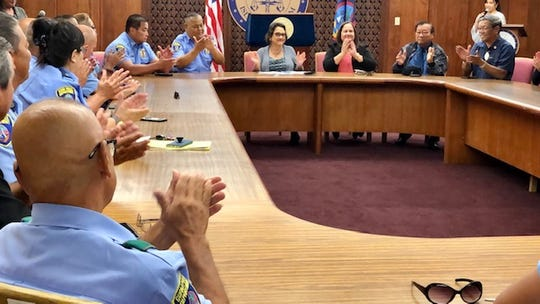 Guam Police Department officers, police reservists and senators applaud as Gov. Lou Leon Guerrero signs into law Sen. Joe San Agustin's bill, doubling the monthly stipend of Guam's police reservists from $250 to $500, during a Jan. 2, 2020 ceremony at Adelup.