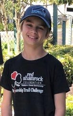 A recent photo of Finn Hall shows a smiling, cancer-free kid wearing a T-shirt promoting the Red Shamrock Foundation started by his father, John Hall.