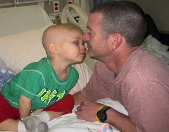 Finn is shown with his father, John Hall, during the nearly 18-month period about ten years ago in which the boy battled cancer through chemotherapy, radiation and immunotherapy.