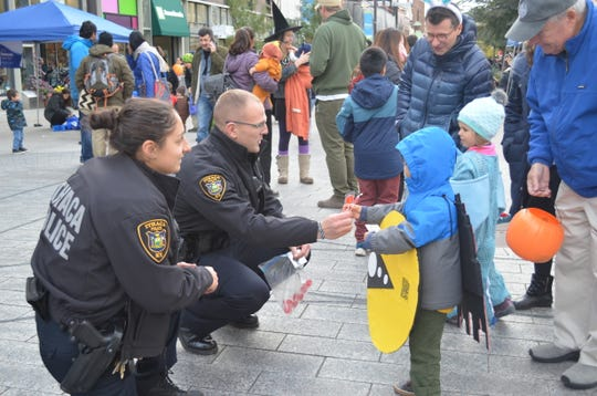 Officer Mary Orsaio interacts with children on the Ithaca Commons while they go trick-or-treating on Halloween.