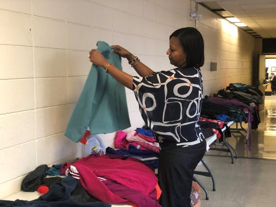 Rhonda Heard, the JMCSS community engagement coordinator, sorts through donated coats for students in need.