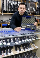 Gun stores like L.E.P.D.  that buy back firearms or do trade-ins have no way to know if those firearms are stolen. Eric Delbert, pictured Dec. 20 with a used gun at L.E.P.D., and others have wanted to change that for years. [Fred Squillante/Dispatch]
