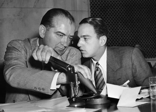 1954: U.S. Sen. Joseph McCarthy, R-Wisconsin, covers the microphones while conversing with his chief counsel, Roy Cohn, during a committee hearing  in Washington, D.C.