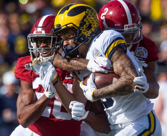 Michigan wide receiver Ronnie Bell (8) is stopped by Alabama defensive back Josh Jobe (28) and defensive back Patrick Surtain, II, (2) in the Citrus Bowl in Orlando, Fla., on Wednesday January 1, 2020.