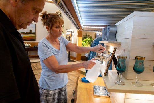 Patti Genko, right, and Scott Beddome, left, check the sparkling wine tap as they set up Bubbles Mobile Bar before a New Year's Eve party at the Clubhouse at Treviso Bay in Naples on Tuesday, December 31, 2019.
