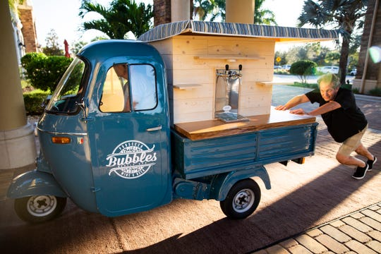 Patti Genko, left, steers one of two 1960s Italian trucks that make up Bubbles Mobile Bar while Scott Beddome, right, pushes it into the Clubhouse at Treviso Bay in Naples on Tuesday, December 31, 2019.