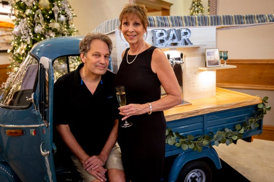 Patti Genko, right, and Scott Beddome, left, pose for a portrait with one of two 1960s Italian trucks that make up Bubbles Mobile Bar before a New Year's Eve party at the Clubhouse at Treviso Bay in Naples on Tuesday, December 31, 2019.