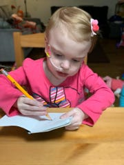 Maci Whisner does some writing practice on her letters.