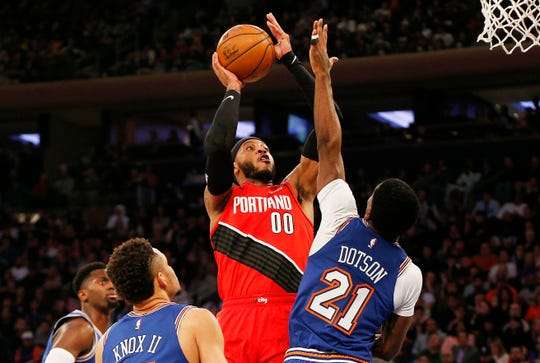 Jan 1, 2020; New York, New York, USA; Portland Trail Blazers forward Carmelo Anthony (00) goes up for a shot while being defended by New York Knicks guard Damyean Dotson (21) during the first half at Madison Square Garden. Mandatory Credit: Andy Marlin-USA TODAY Sports