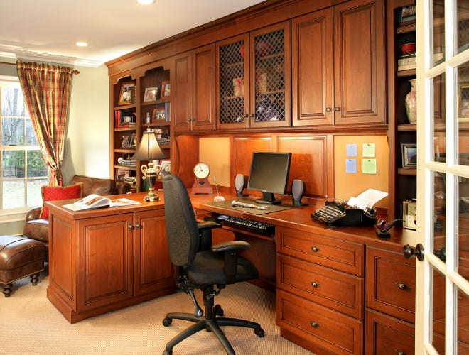 Cherry cabinetry highlights this home office by Thyme and Place Design in Wyckoff, NJ.