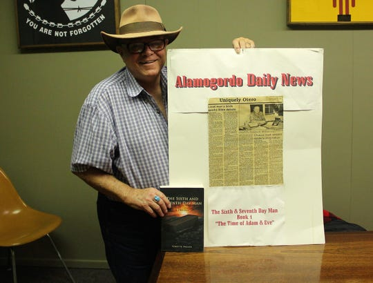 "Alamogordo author Robert M. Pollack holds a copy of his book ""The Sixth and Seventh Day Man: A Trilogy"" and a poster with a story the Alamogordo News Published about his first book in the trilogy in 1995."