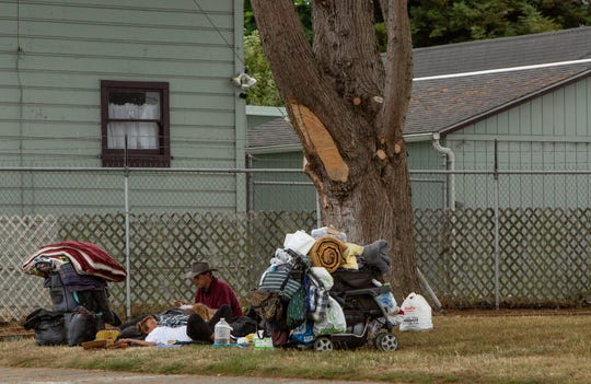 A man and woman rest and eat on a grassy patch surrounded by belongings in Eureka on Aug. 21, 2019.