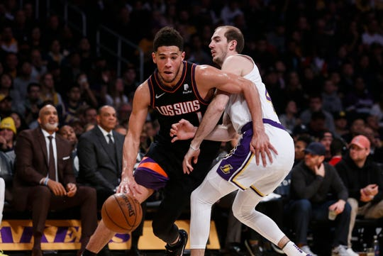 Phoenix Suns' Devin Booker (1) drives past Los Angeles Lakers' Alex Caruso (4) during the first half of an NBA basketball game, Wednesday, Jan. 1, 2020, in Los Angeles. (AP Photo/Ringo H.W. Chiu)