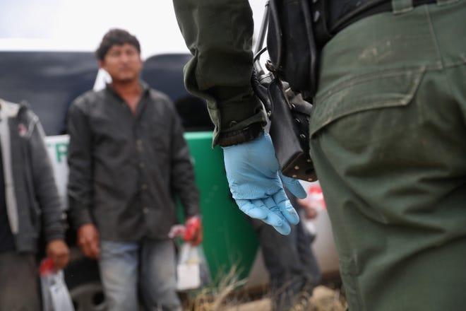 Un agente de la patrulla fronteriza detiene a un grupo de migrantes en Texas.