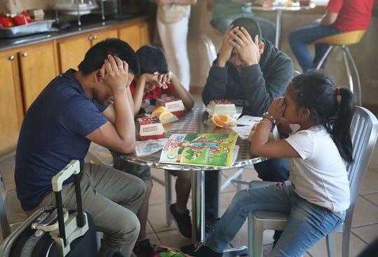 Una familia ora antes de consumir sus alimentos en un albergue de inmigrantes en Texas.