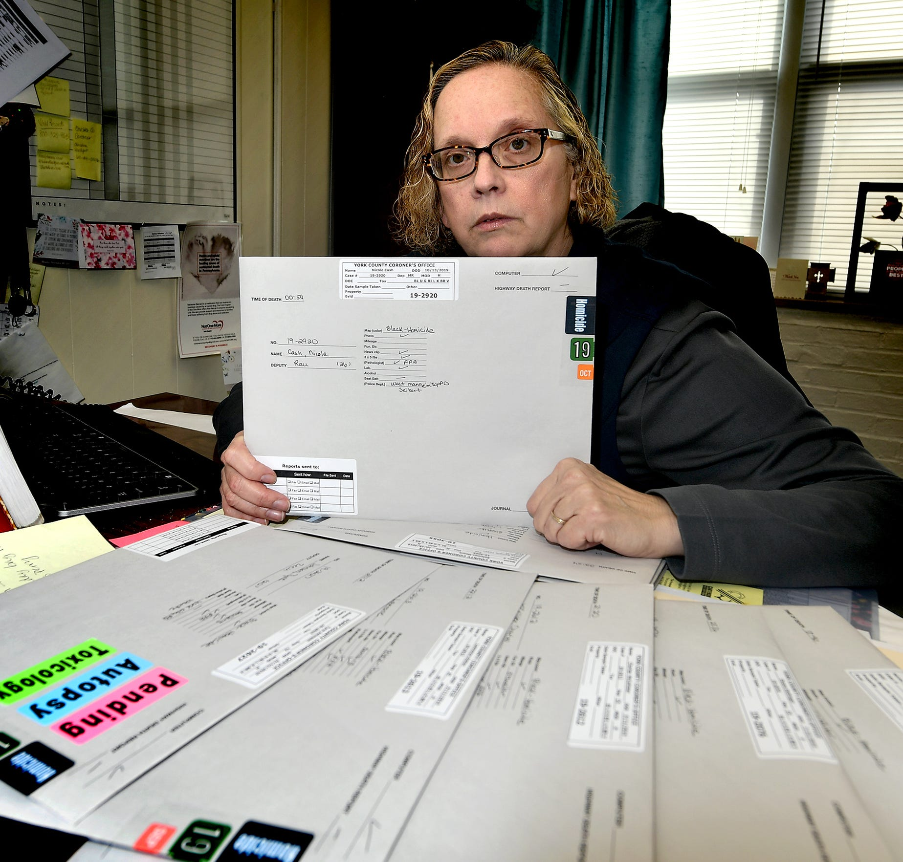 York County Coroner Pam Gay poses with some of the year's homicide reports at her office Thursday, Jan. 2, 2020. There were 16 homicides in York City in 2019. Bill Kalina photo