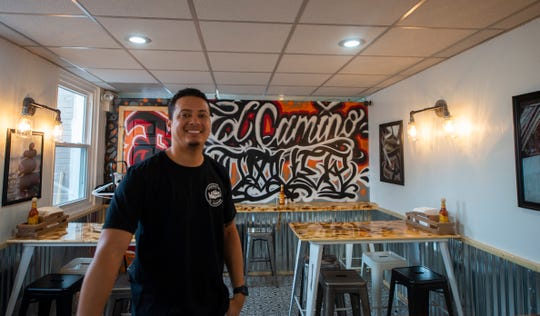 "Owner Ethan Greer stands inside the dining room at Taqueria El Camino in Dover. Taqueria is decorated with murals and artwork from 15 local artists including this dining room mural designed by  Jeremy ""Jay Rock"" Wibel of York. The restaurant is expected to open Tuesday, Jan. 7, 2020."