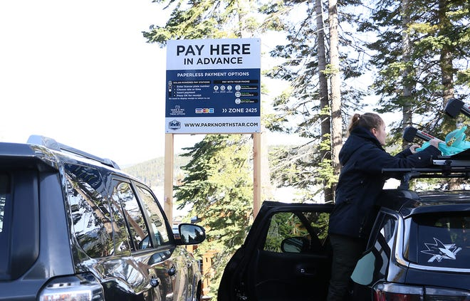 A snowboarder prepares to hit the slopes after parking in the pay to park lot of the Northstar California Ski Resort near Truckee on Jan. 2, 2020.