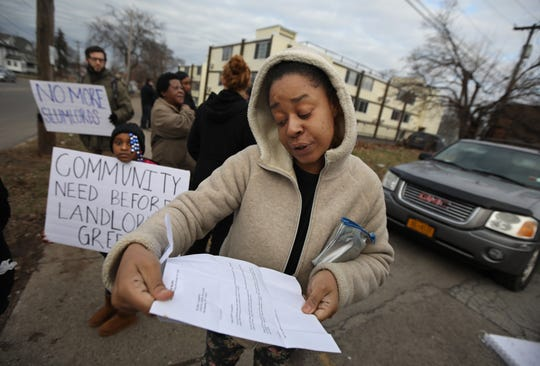 Resident Kesha Campbell reads the eviction letter she got as she stands outside the Clinton Lofts apartment complex at 1624 N. Clinton Ave. in Rochester on Thursday, Jan. 2, 2020.  The letter, dated Dec. 31, 2019, tells her she vacate her apartment by Jan. 31, 2020.