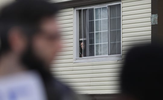 A tenant peeks out her second-floor window as people protest evictions from the Clinton Lofts apartment complex at 1624 N. Clinton Ave. and two other apartment buildings in Rochester Thursday, Jan. 2, 2020.