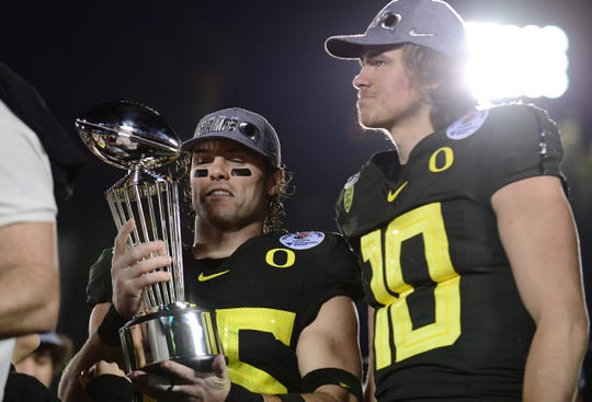 Oregon Ducks safety Brady Breeze (25) and quarterback Justin Herbert (10) celebrate with the Leishman Trophy on the podium after the Oregon Ducks defeated the Wisconsin Badgers during the 106th Rose Bowl game at Rose Bowl Stadium.