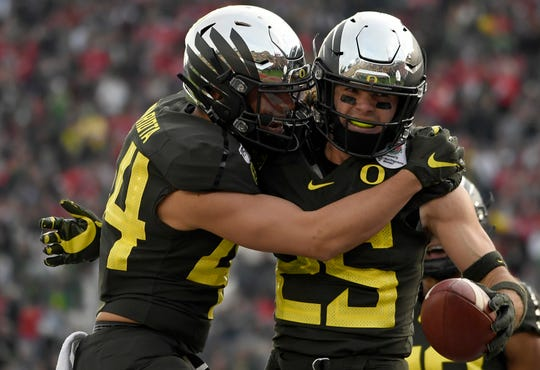 Brady Breeze #25 of the Oregon Ducks celebrates with Matt Mariota #44 after scoring a 31 yard touchdown off of a recovered fumble on a punt by the Wisconsin Badgers during the third quarter in the Rose Bowl game presented by Northwestern Mutual at Rose Bowl on January 01, 2020 in Pasadena, California.