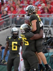 Oregon Ducks quarterback Justin Herbert (10) celebrates scoring a touchdown with Oregon Ducks offensive lineman Dallas Warmack (75) in the second quarter against the Wisconsin Badgers during the 106th Rose Bowl game at Rose Bowl Stadium.