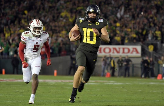 Oregon Ducks quarterback Justin Herbert (10) runs against Wisconsin Badgers cornerback Rachad Wildgoose (5) in the fourth quarter during the 106th Rose Bowl game at Rose Bowl Stadium.