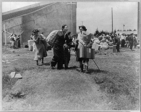 Two Japanese evacuee families meeting at assembly center, Salinas Rodeo Grounds in March 1942.