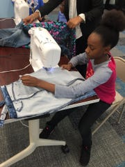 Children learn how to seam pants during sewing lesson taught by Sewority House.