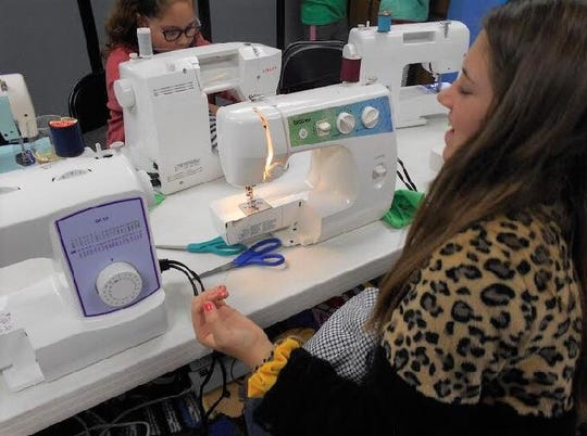 Children practice sewing skills at Angelo West Branch Library.