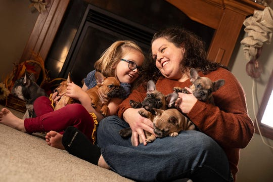 Kelly Morris and her daughter, Alayna, with a litter of French Bulldogs at their Brandon-based breeding company.