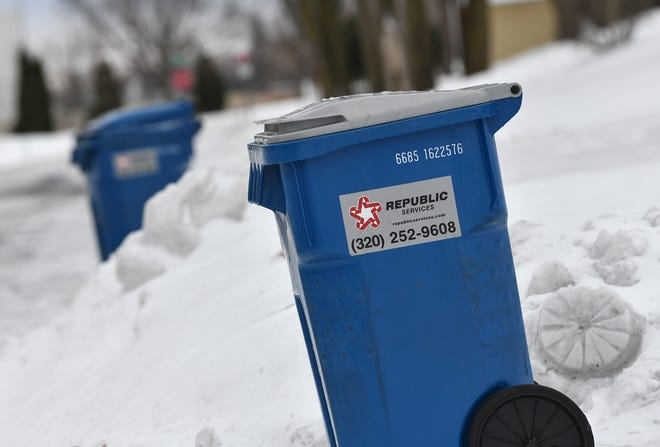 Household recycling containers line a street Thursday, Jan. 2, 2019, in Sartell.