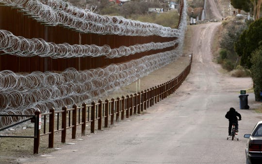 A boy rides his bike along a razor-wire-covered border wall that separates Nogales, Arizona, from Nogales, Mexico, on the other side Saturday, March 2, 2019.