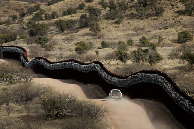 This March 2, 2019, photo shows an agent patrolling on the U.S. side of a razor-wire-covered border wall along the Mexican border east of Nogales, Arizona.