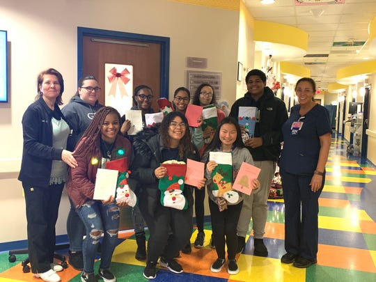 Several Millville High School AVID 12 students brought holiday cheer in the form of stockings and gifts for children to Inspira Health on Dec. 23.