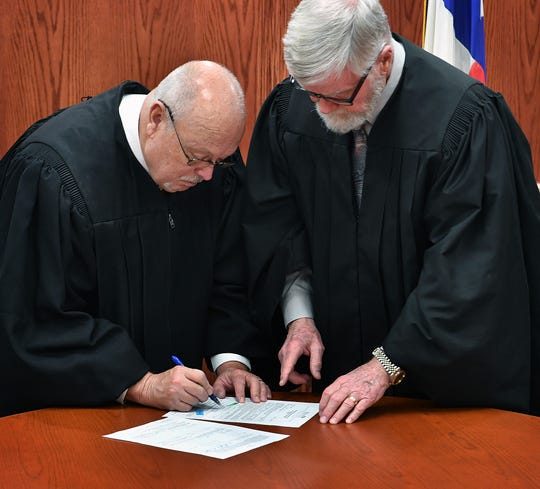 Judge Mike Little, left, signs official papers after being sworn in as interim Justice of the Peace, Precinct 1 Place 1 by Wichita County Judge Woody Gossom Thursday morning.